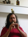 Playing a recorder with a cockatiel on his head.