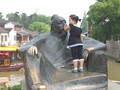 A small kid covering a wise-looking statue's mouth. It is cute.